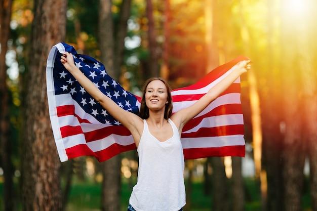 Dziewczyna macha amerykańską flagę.