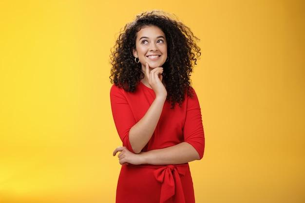 Dziewczyna mająca ciekawy pomysł, uśmiechnięta, bo pewnie plan może zadziałać. urocza szczęśliwa kobieta z kręconymi włosami w czerwonej sukience patrząca w lewy górny róg zamyślona, myśląca nad żółtą ścianą.