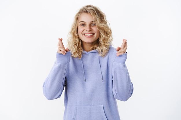 Dziewczyna mająca wiarę, że wszystko się spełni stojąc optymistycznie i z nadzieją z optymistycznym, pozytywnym uśmiechem ze skrzyżowanymi palcami na szczęście modląc się, życząc i marząc o dobrym wyniku nad białą ścianą