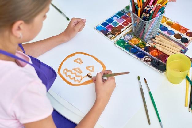 Dziewczyna malarstwo w klasie sztuki na halloween