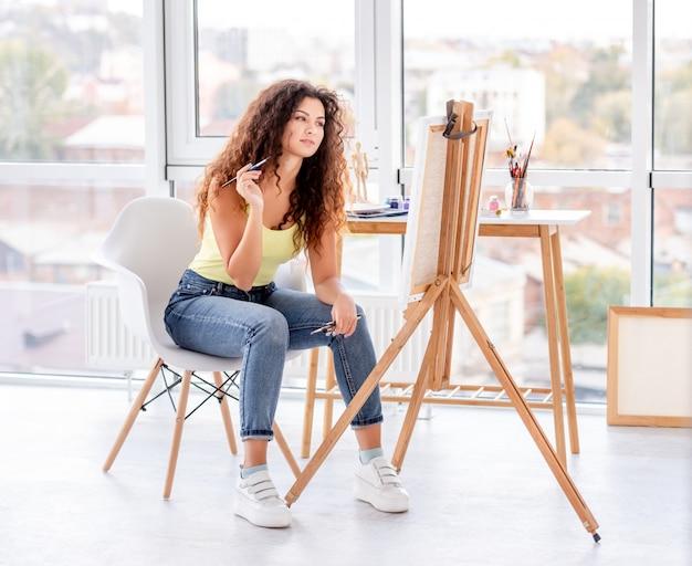 Dziewczyna malarz robi nowemu obrazowi
