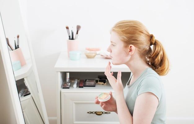 Dziewczyna malowała trądzik na twarzy przed lustrem