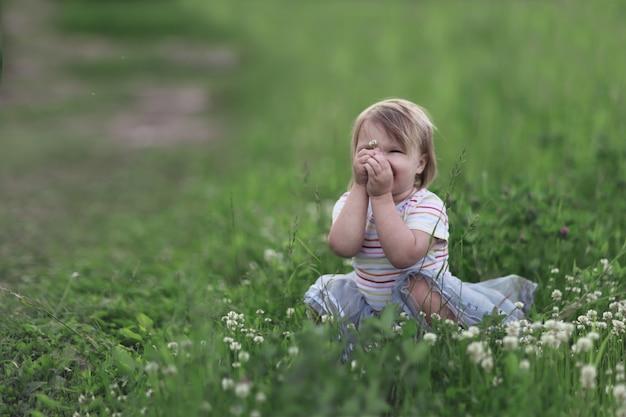 Dziewczyna maluch bawi się w chowanego na zielonej polanie