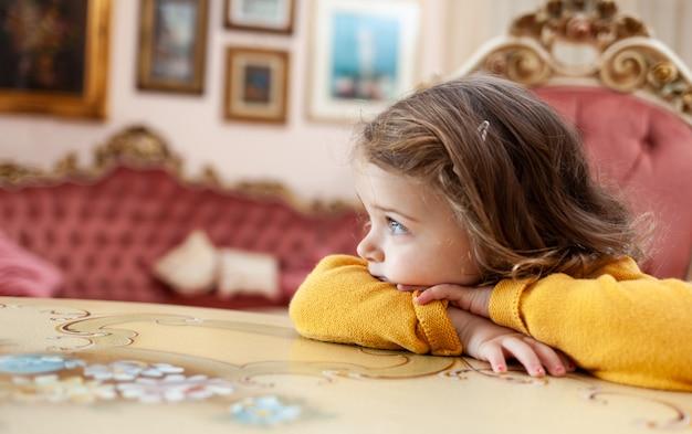 Dziewczyna maluch w salonie z barokowym wystrojem.