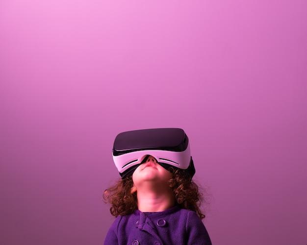 Dziewczyna Malucha Kręcone Włosy W Okularach Wirtualnej Rzeczywistości I Fioletowe Ubrania Patrząc W Górę Premium Zdjęcia