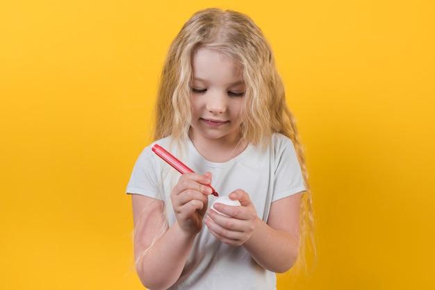 Dziewczyna maluje jajko z odczuwanym piórem