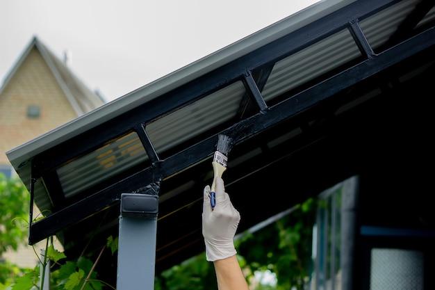 Dziewczyna maluje pędzlem czarny metal. maluje dach. selektywne skupienie