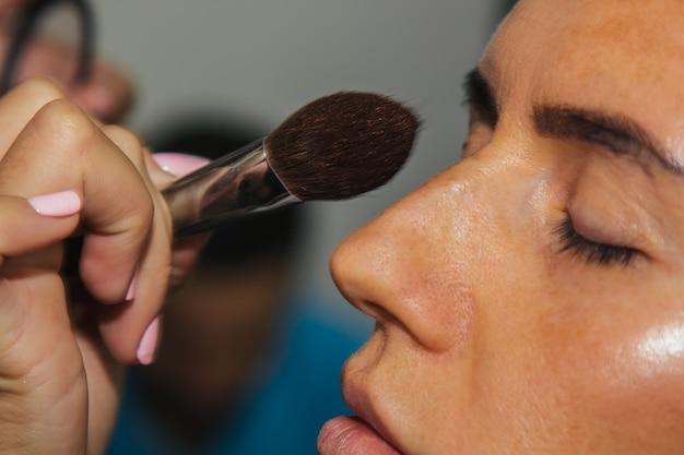 Dziewczyna maluje puder na twarz, uzupełnia makijaż smokey eyes w salonie piękności. profesjonalna pielęgnacja skóry.