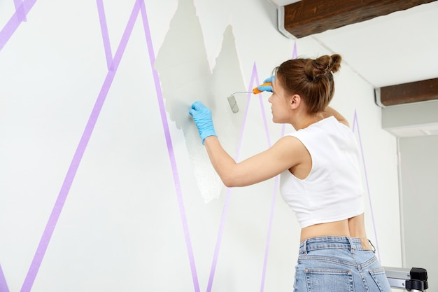Dziewczyna maluje ścianę małym wałkiem do malowania i używa taśmy maskującej stojąc na drabinie