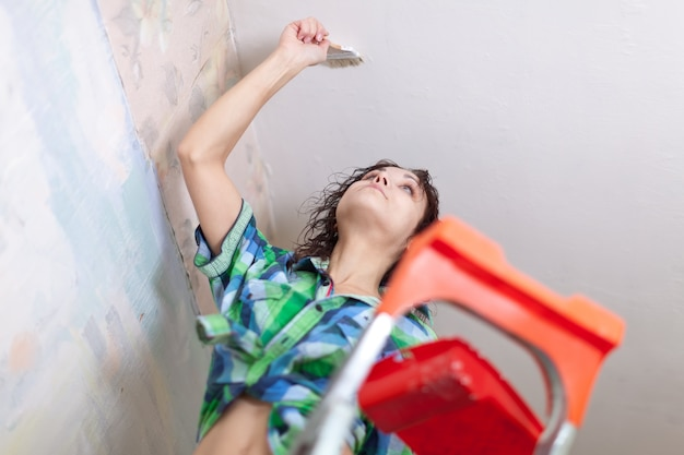 Dziewczyna maluje sufit w domu