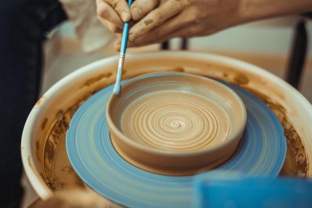 Dziewczyna maluje talerz gliny na kole garncarskim