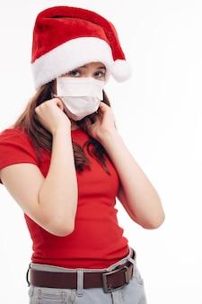 Dziewczyna maska medyczna czerwona koszulka świąteczna czapka w studio