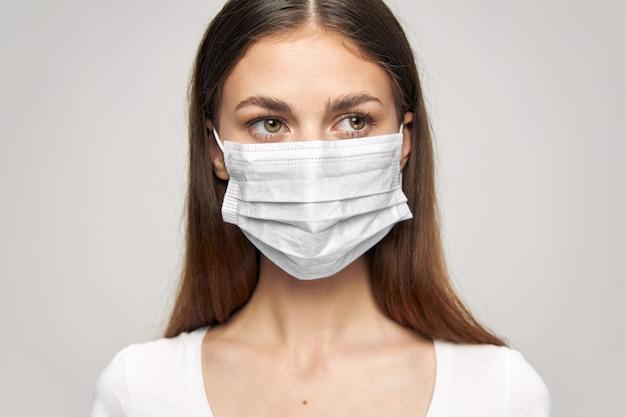 Dziewczyna maska medyczna z boku wyglądają bezpieczeństwa na tle światła