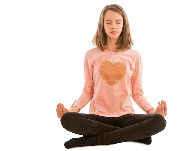 Dziewczyna medytuje siedząc w pozycji lotosu na białym tle