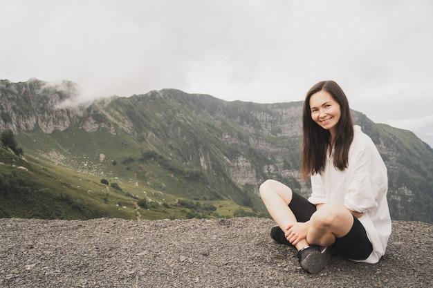 Dziewczyna medytuje w górach joga rekolekcje na łonie natury dziewczyna w białej koszuli cieszy się piękn...