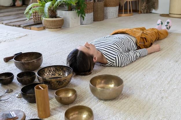 Dziewczyna medytuje z misami podczas tybetańskiego masażu i terapii dźwiękiem tybetańskich praktyk duchowych