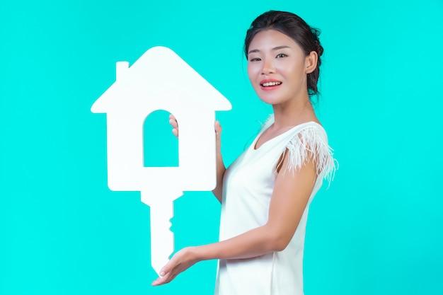 Dziewczyna miała na sobie białą koszulę z długimi rękawami z kwiatowym wzorem, trzymającą symbol domu i pokazującą różne gesty w kolorze niebieskim.