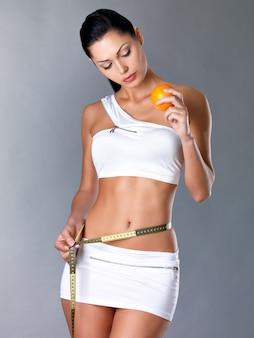 Dziewczyna mierzy sylwetkę miarką i trzyma pomarańczę. cocnept zdrowego stylu życia.