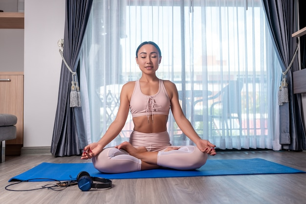 Dziewczyna mieszanej rasy pozuje z przyjemnością wykonuje rozciąganie, siedzi w pozycji lotosu i cieszy się medytacją