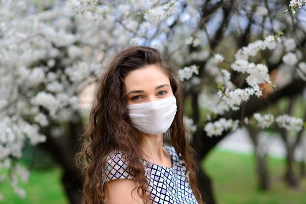 Dziewczyna, młoda kobieta w ochronnej sterylnej masce medycznej na twarzy w wiosennym ogrodzie. zanieczyszczenie powietrza, wirus, koncepcja koronawirusa pandemicznego.