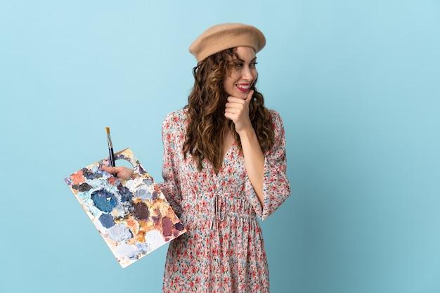 Dziewczyna młody artysta trzyma paletę na białym tle na niebieskiej ścianie, patrząc z boku i uśmiechnięty