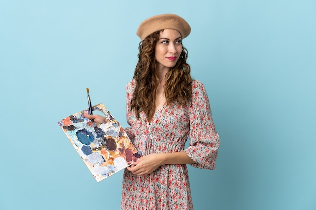 Dziewczyna młody artysta trzyma paletę na białym tle na niebieskim tle, patrząc z boku
