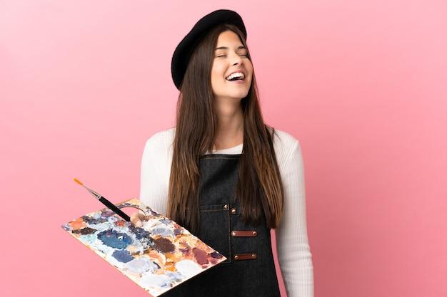 Dziewczyna młody artysta trzymając paletę na białym tle różowym śmiechem