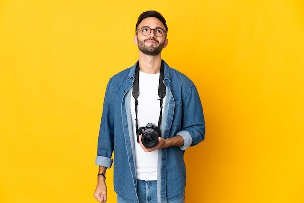 Dziewczyna młody fotograf na białym tle na żółtym tle i patrząc w górę