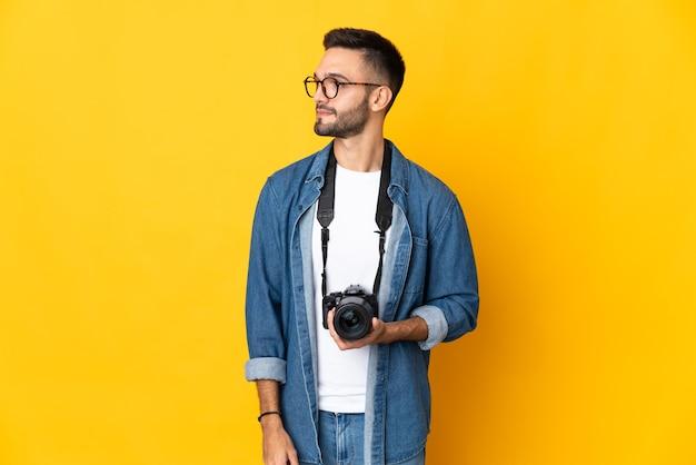 Dziewczyna młody fotograf na białym tle na żółtym tle, patrząc z boku