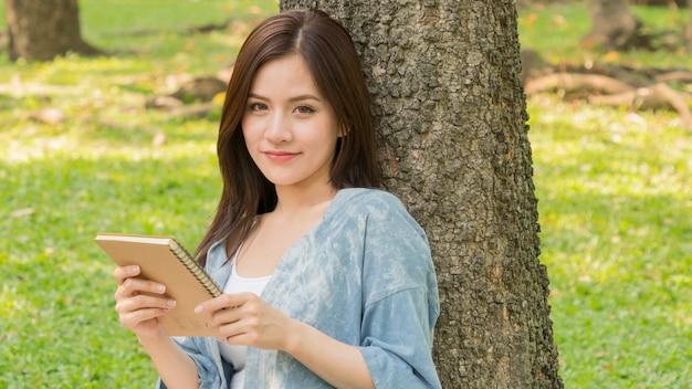 Dziewczyna moda używać książki i czytać w parku ogrodowym