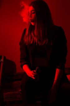 Dziewczyna model pali vape w czerwonym świetle.