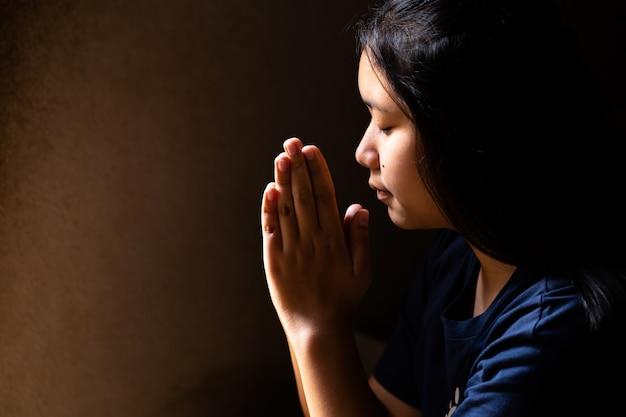 Dziewczyna modli się z zamkniętymi oczami