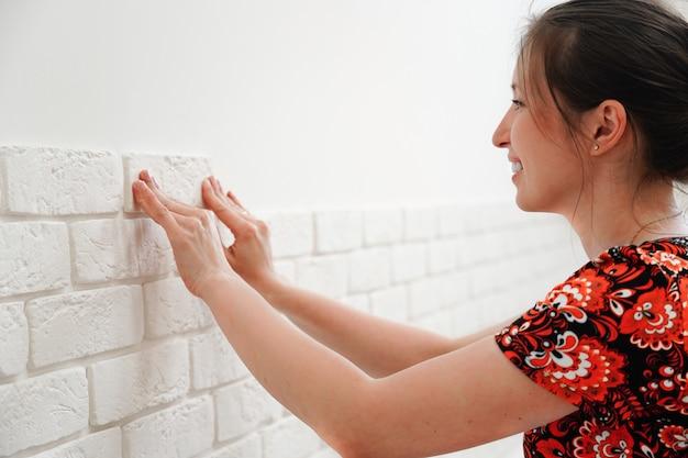 Dziewczyna montuje dekoracyjną cegłę