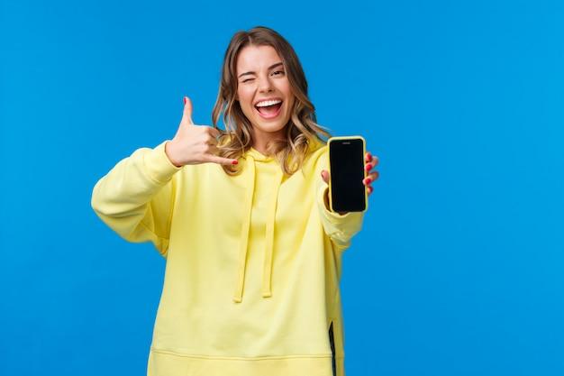 Dziewczyna mówi: uderz mnie, gdy próbuję zdobyć numer faceta, trzymając smartfon, pokazując wyświetlacz telefonu komórkowego, mrugając i wykonując gest telefoniczny, poproś o telefon, stojąc
