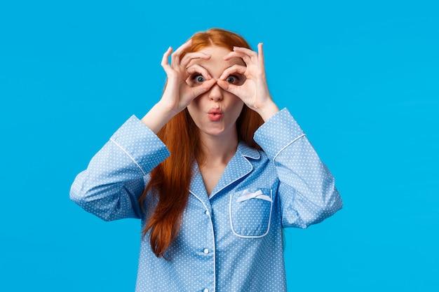 Dziewczyna mówiąca wow, wpatrując się zaskoczona, widząc świetną okazję na specjalne zniżki na wakacje. atrakcyjna ruda kobieta w piżamie, patrząc przez palce i składane usta, rozbawiona, niebieska ściana