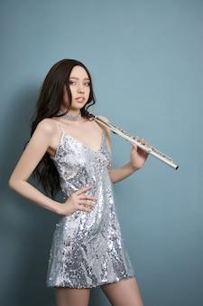 Dziewczyna muzyk z fletem w dłoniach w ubraniach scenicznych. kobieta gra na flecie