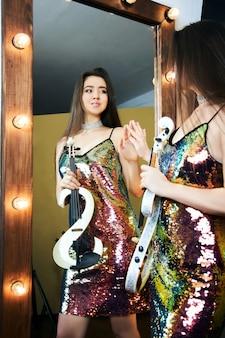 Dziewczyna muzyk ze skrzypcami w dłoniach w strojach scenicznych. kobieta gra na współczesnych skrzypcach