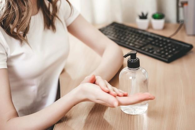 Dziewczyna myje ręce żelowym środkiem antyseptycznym i stosuje antybakteryjny alkohol do higieny rąk przed bakteriami koronawirusowymi, pandemią, kwarantanną. butelka środka antyseptycznego na stole