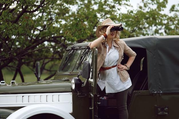 Dziewczyna myśliwy w pobliżu samochodu safari