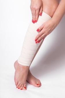 Dziewczyna na białym koryguje elastyczny bandaż, który wiąże