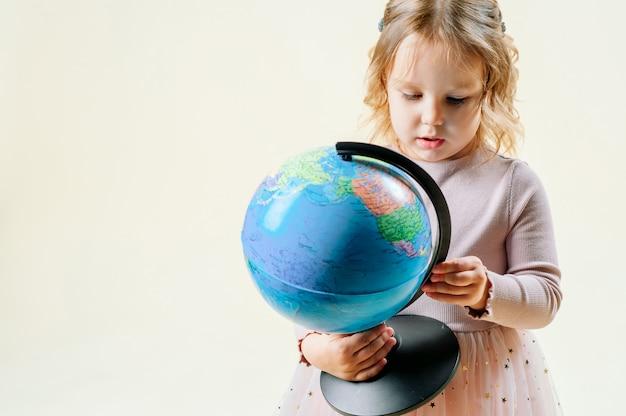 Dziewczyna na białym tle trzyma glob, w pobliżu stoi walizka