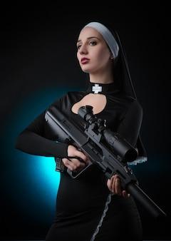 Dziewczyna na czarnym tle w sukience zakonnicy pozuje z pistoletem, celując, strzelając