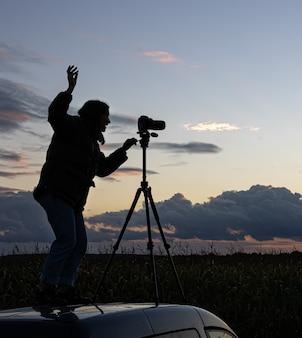 Dziewczyna na dachu samochodu fotografuje zachód słońca ze statywem