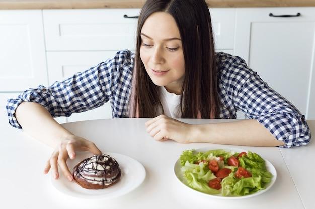 Dziewczyna na diecie wybiera, co jeść między sałatką a bułeczką cynamonową