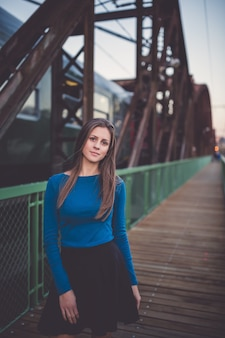 Dziewczyna na dworcu kolejowym z odjeżdżającym pociągiem miejski portret zachodu słońca