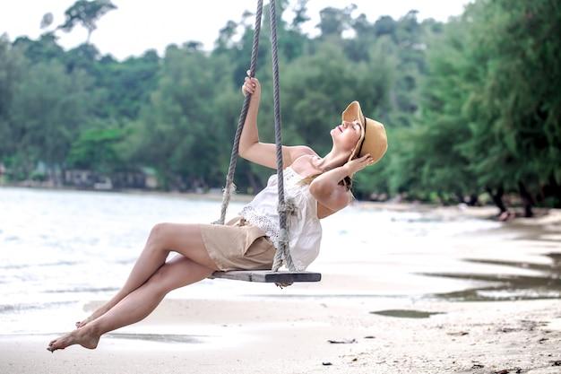 Dziewczyna na huśtawce na plaży w tajlandii