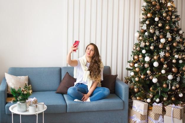 Dziewczyna na kanapie, robiąc selfie, wyciągnięta ręka, święta nowego roku, zbliżają się święta bożego narodzenia, nagrywanie powitania w aparacie i miejsce na tekst