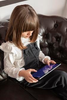 Dziewczyna na kanapie z tabletem