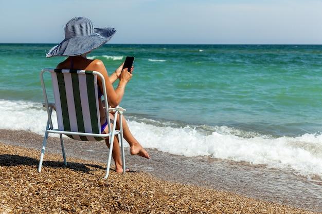 Dziewczyna na leżaku nad morzem patrzy na telefon
