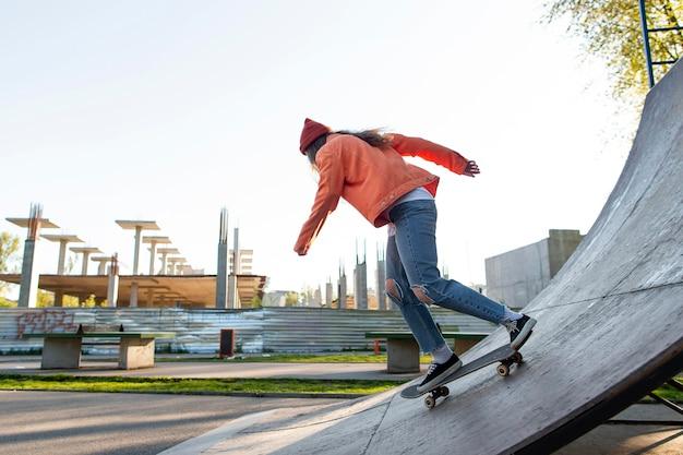 Dziewczyna na łyżwach na rampie pełny strzał